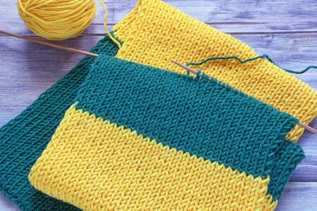 Knitting. Striped scarf with knitting needles and ball of wool on rustic background 写真素材
