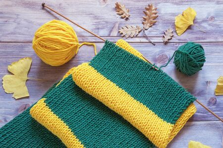 Knitting on autumn day. Warm striped yellow-green scarf with knitting needles and balls of wool on rustic background