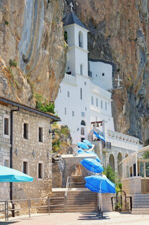 Religious architecture.  Ostrog monastery, located in almost vertical rock. View of road to temple with blue sun umbrellas on sunny summer day. Montenegro