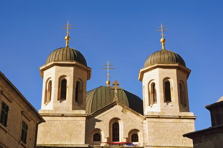 Religious architecture. Montenegro, Old Town of Kotor. Domes of Orthodox Church of St. Nicholas against blue sky 写真素材