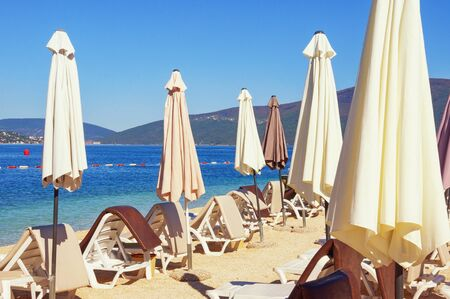 Summer vacation concept.  Sunny day on beach. Lounge chairs with sun umbrellas.  Montenegro, Adriatic Sea, Bay of Kotor