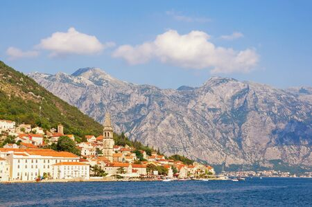 Beautiful Mediterranean landscape on sunny summer day. Montenegro, Adriatic Sea, Bay of Kotor. View of ancient town of Perast , bell tower of church of St. Nicholas