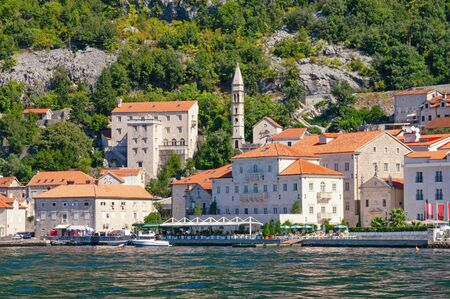 Montenegro. View of ancient town of Perast on sunny autumn day. Bell tower of Church of Our Lady of Rosary. Adriatic Sea, Kotor Bay