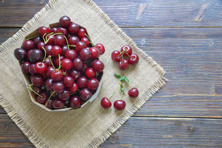 Fresh ripe cherries in cardboard box on rustic table. Flat lay. Free space for text