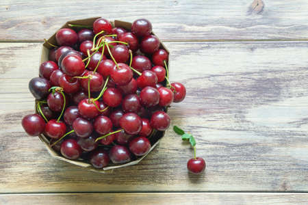 Cherries from market.  Fresh ripe fruits in cardboard box on rustic table. Flat lay. Free space for text