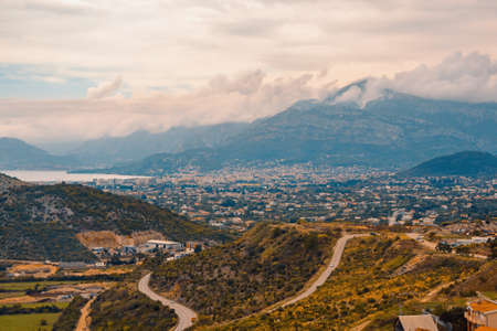 Autumn Mediterranean landscape on cloudy misty day. Autumn Balkan road trip: clouds, mountains, hills and roads. Montenegro, view of Dobra Voda town