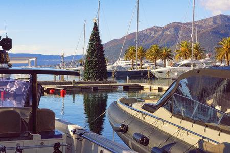 Tivat / Montenegro - December 13 2020:  Christmas Tree in yacht marina. View of Porto Montenegro Marina in Tivat city on sunny winter day. Montenegro, Adriatic Sea, Kotor Bay