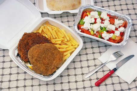 Food delivery. Bread, salad and pljeskavica - grilled dish of minced meat, french fries in takeaway containers