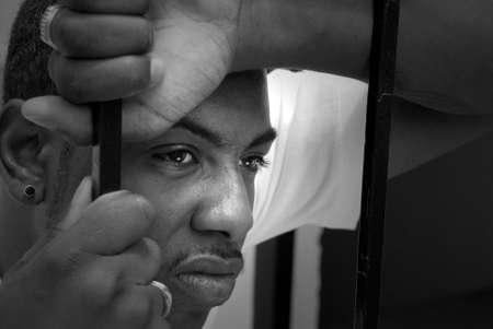 rejas de hierro: La cara de un hombre africano americano enojado tras las rejas de hierro
