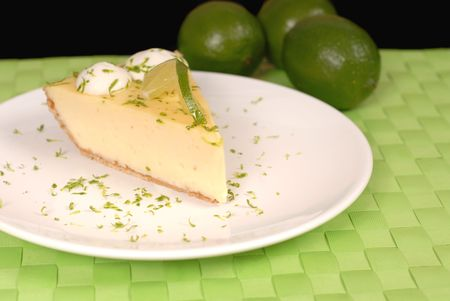 Key lime pie on white plate with lime zest and limes Stok Fotoğraf
