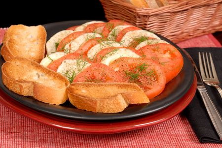 A fennel and tomato salad with crostini on a black plate