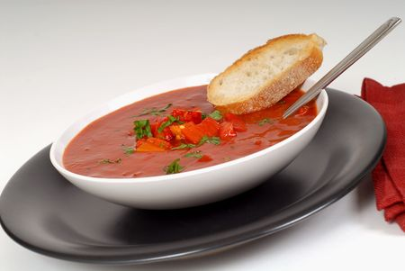A tomato, red pepper, basil soup in white bowl with bread and spoon on a light gray background