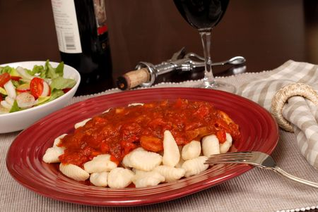 Delicious potato gnocchi with marinara sauce with a salad and wine