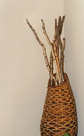 A woven basket with several sticks in it
