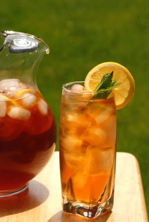A glass of iced tea with pitcher of tea next to it