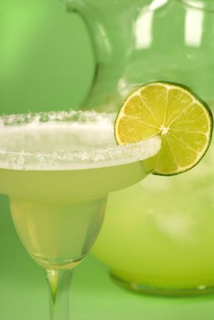 A close up of a margarita with a pitcher of margaritas