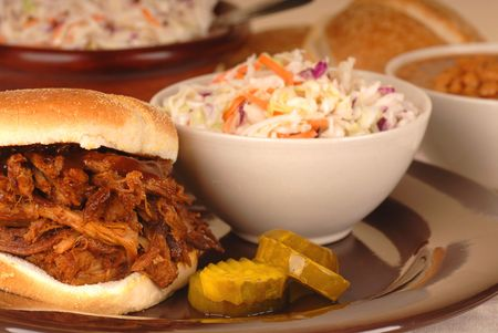 A pulled pork sandwich with cole slaw and beans