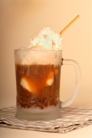 A root beer float in frosted glass and straw