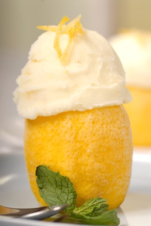Two Lemon sorbets in a frozen lemon shell with mint and a shallow depth of field