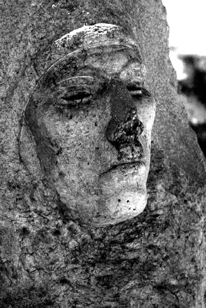 Scary and eerie face of a woman carved in granite at a cemetery gravesite