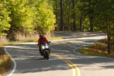 Lone motorcyclist riding along a winding forested road