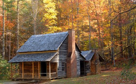 A log cabin in a wooded setting during the autumn season Foto de archivo