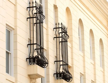 Wrought iron bars around two windows of a white building Banco de Imagens
