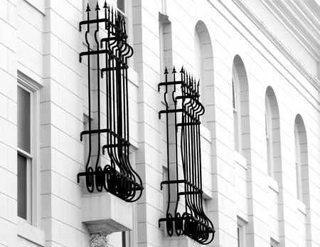 A black and white image of wrought iron around two windows of a white building Banco de Imagens