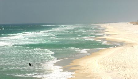 A lone surfer on a beach in Pensacola, Florida Stock Photo
