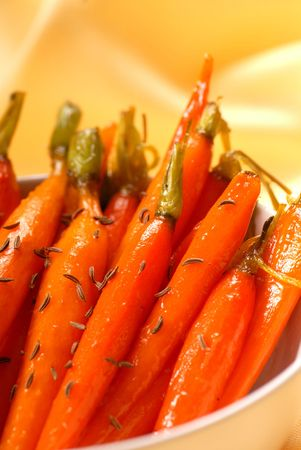 Fresh organic honey glazed carrots served with caraway seeds