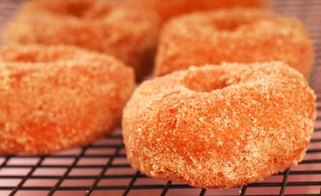 Freshly made strawberry doughnuts with a sugar coating cooling on a wire rack