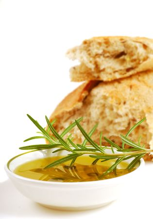 Bowl of extra virgin olive oil and crusty bread with a sprig of rosemary