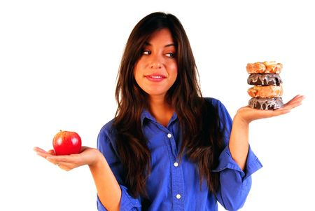 Attractive young woman deciding to eat a healthy apple or unhealthy donut Banco de Imagens