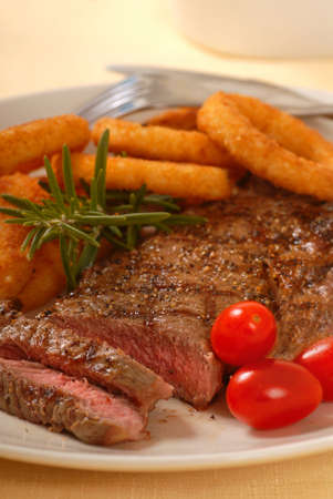 rib eye: Delicious grilled rib eye steak with onion rings Stock Photo