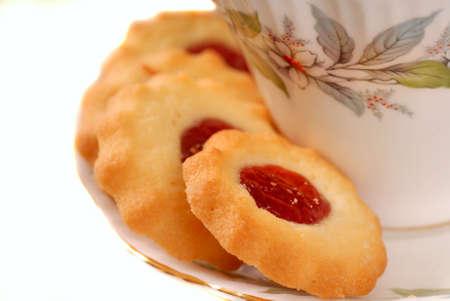 empreinte du pouce: Framboise empreinte cookies sur une soucoupe avec une tasse de th�
