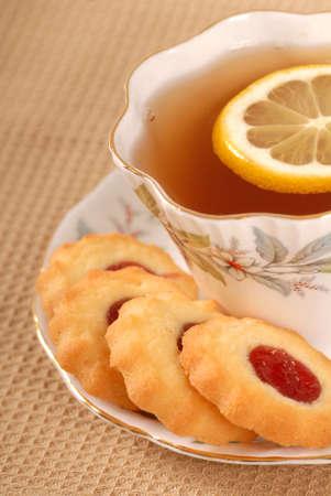 odcisk kciuka: Świeżo upieczone ciasteczka malina odcisk kciuka z filiżanką herbaty