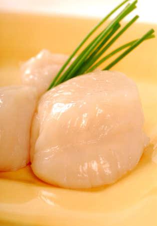 cebollin: Dos de mar fresca y cruda vieiras con una guarnici�n de ceboll�n Foto de archivo
