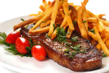 Freshly grilled steak with French Fries, parsley and tomatoes