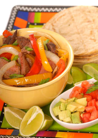 condiments: Fajitas platter containing beef, peppers, onions and condiments