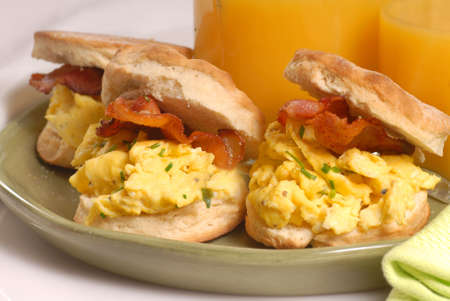 Scrambled egg and bacon biscuit with orange juice photo