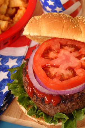 catsup: Freshly grilled hamburger in a 4th of July setting