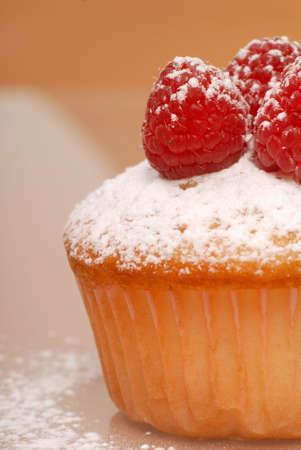 Closeup of freshly baked vanilla cupcake with raspberries and powdered sugar