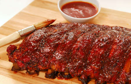 bbq sauce: Slab of freshly grilled BBQ spare ribs with dipping sauce Stock Photo
