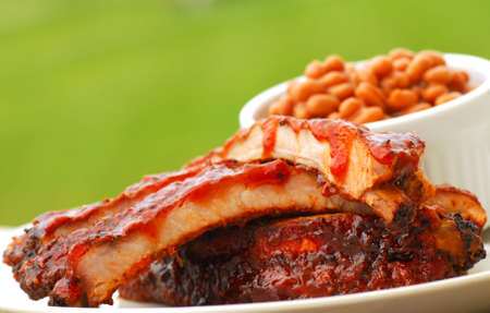 Freshly grilled BBQ Ribs and beans in an outdoor setting Stock Photo