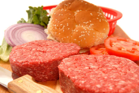 Picnic ingredients for cheeseburgers including patties, tomato, onion and lettuce photo