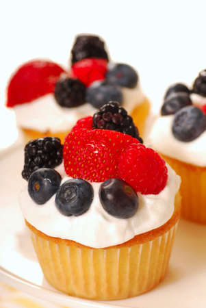 Freshly baked vanilla cupcakes with fresh berries and whipped cream photo