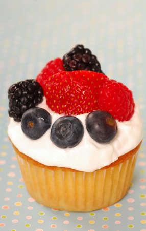 Vanilla cupcake with fresh berries and whipped cream photo