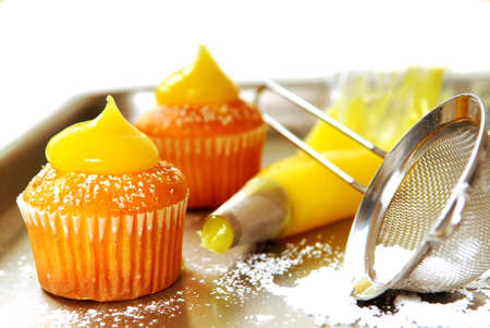 Decorating vanilla cupcakes with lemon curd and powdered sugar