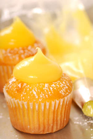 curd: Decorating vanilla cupcakes with lemon curd and powdered sugar