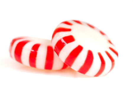 Two pieces of red and white peppermint Christmas candy